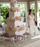 Four layer white wedding cake with flower decorations