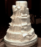 White wedding cake with buttons, lace, and bow