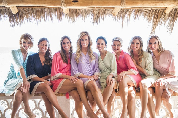 a bride and her bridesmaids sitting on railing of hotel in mexico in blue pink purple green robes