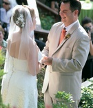 Bride and groom hold hands at alfresco wedding ceremony