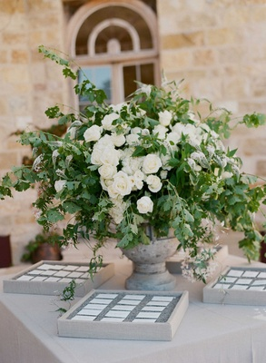 Light grey stone urn white rose flower arrangement greenery escort cards in boxes with tan linens