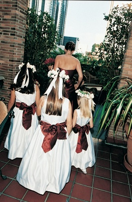 Flower girls walk down the aisle in white dresses and red sashes