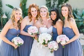 Bride in Oscar de la Renta strapless wedding dress with bridesmaids in strapless purple dresses