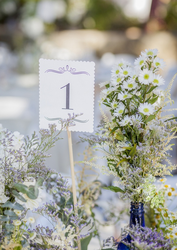 small white card purple calligraphy table 1 and white and green wildflower floral arrangements