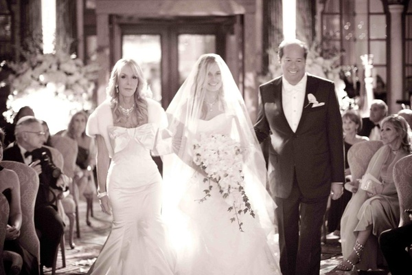 Black and white photo of bride escorted down aisle by mom and dad