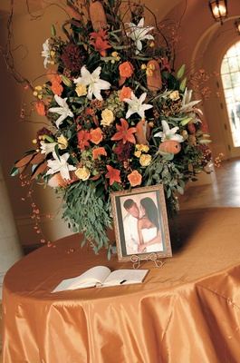 guest book, photo and flowers placed on orange table