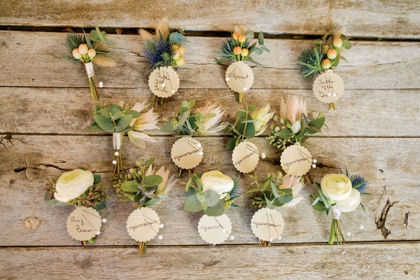 collection of rustic-chic boutonnieres with sea holly, roses, and orange buds