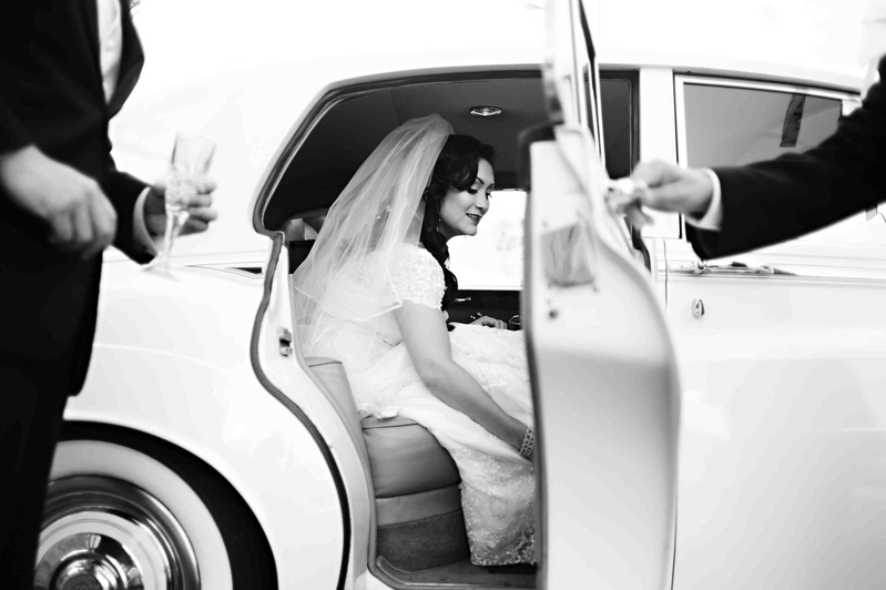 Black and white photo of bride exiting vintage car