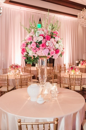 wedding reception centerpiece with pink roses on clear vase, white vases