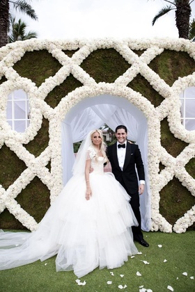 Bride in full tulle skirt and groom in front of rose wall