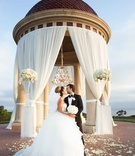 newlyweds kiss under dome pelican hill resort newport beach california pnina tornai dress drapery