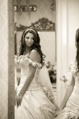 Sepia tone picture of bride looking in mirror
