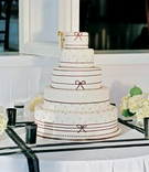 five-tiered white cake with thin black ribbons and dots