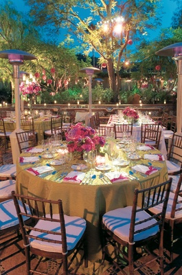 Green reception table under trees with pink centerpiece