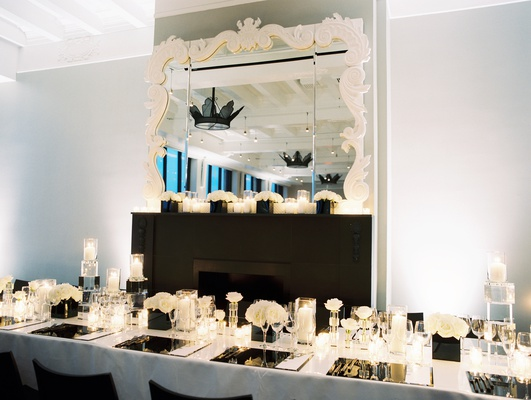 modern, chic black and white wedding reception black chairs, white linens, framed mirror