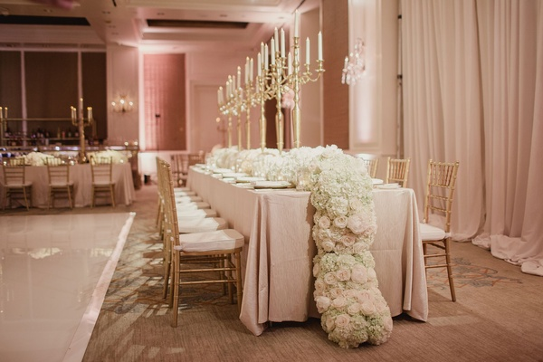 Wedding reception in ballroom with king's table candelabrum and lush flower centerpiece flowing