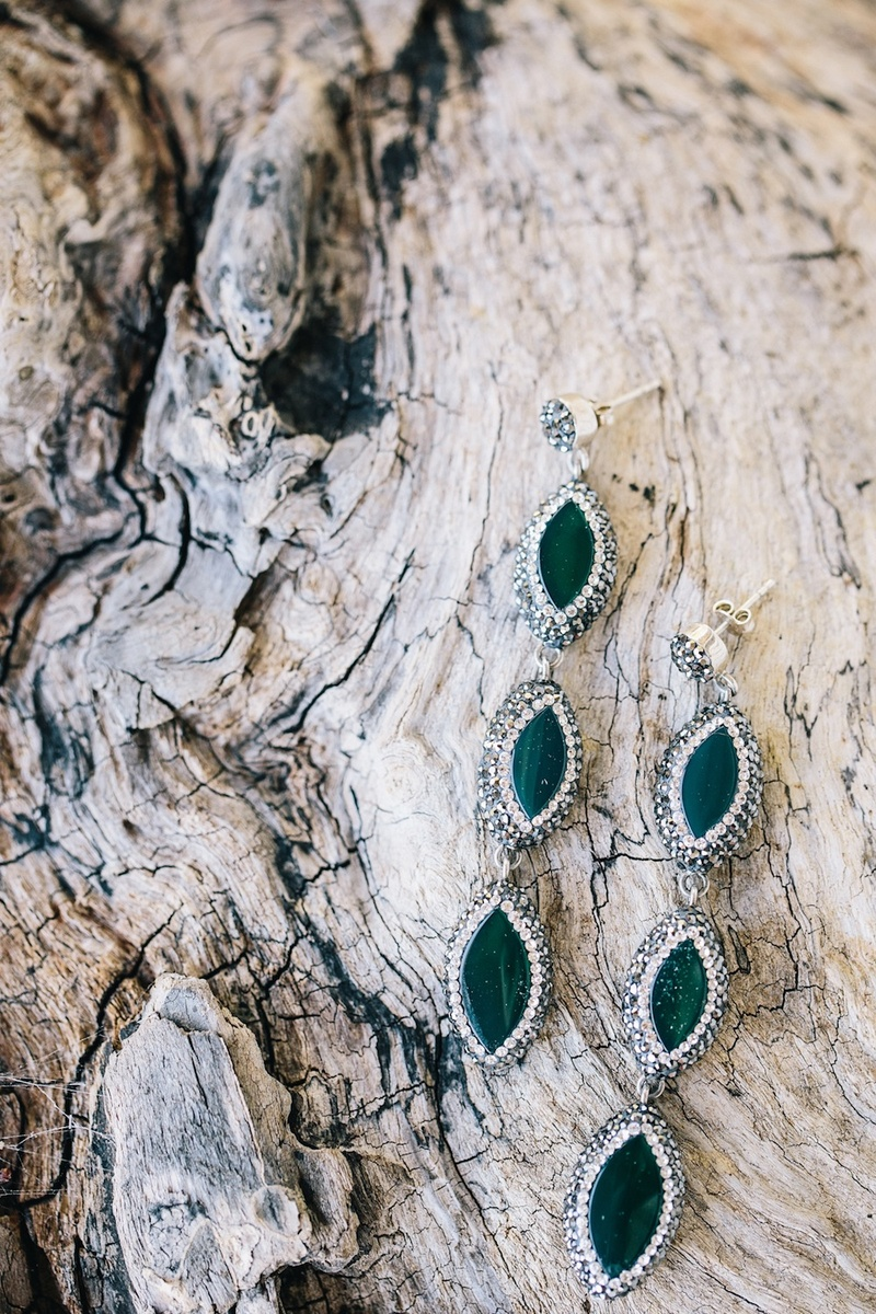 Emerald stones with halo setting on tree bark