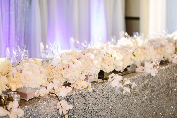 orchids and roses line head table with silver sequin table cloth flower garland runner