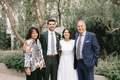 wedding photo of groom and bride with father of groom in navy suit and mother of groom dress shirt