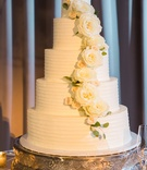 5 tier cake with white frosting and white roses and green leaves curving down cake