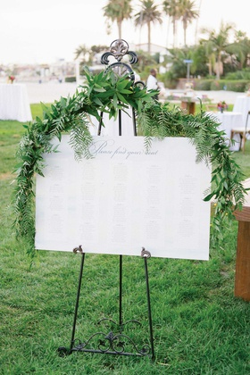Outdoor wedding reception hotel wedding white seating chart on wrought iron easel greenery ferns