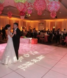 Bride in a Vera Wang gown dances with groom in a black tuxedo