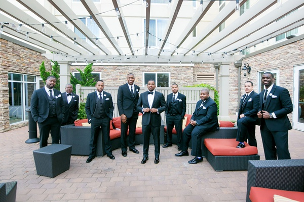 groom and groomsmen in black tuxedos in outdoor lounge area
