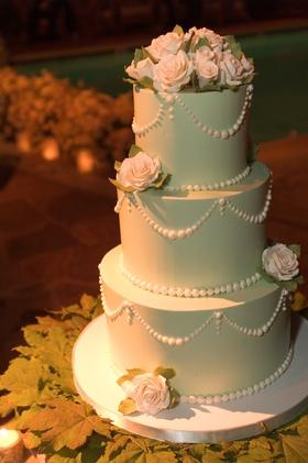 Light green, three-tier wedding cake with light pink roses