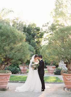 Bride in wedding dress and veil touching foreheads of groom in tuxedo natural bouquet greenery