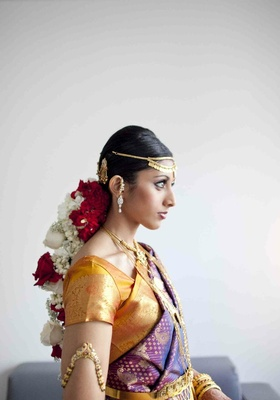 Actress Reshma Shetty wears a purple and gold lehenga, flowers in her hair, and gold jewelry