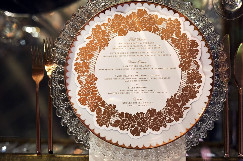 wedding reception clear charger plate with gold copper rose menu design circle motif flatware