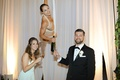 Wedding guests with champagne flutes acrobatic performer server aerial dancer pour drinks