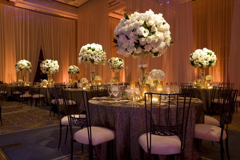 Wedding reception with Chameleon Chairs and tables with tall arrangements of light flowers