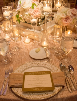 Place setting with menu, centerpieces with roses and candles