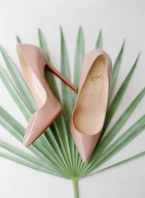 Wedding shoes nude tan Christian Louboutin heels with red soles on green palm frond