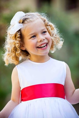 White flower girl dress with pink-orange sash