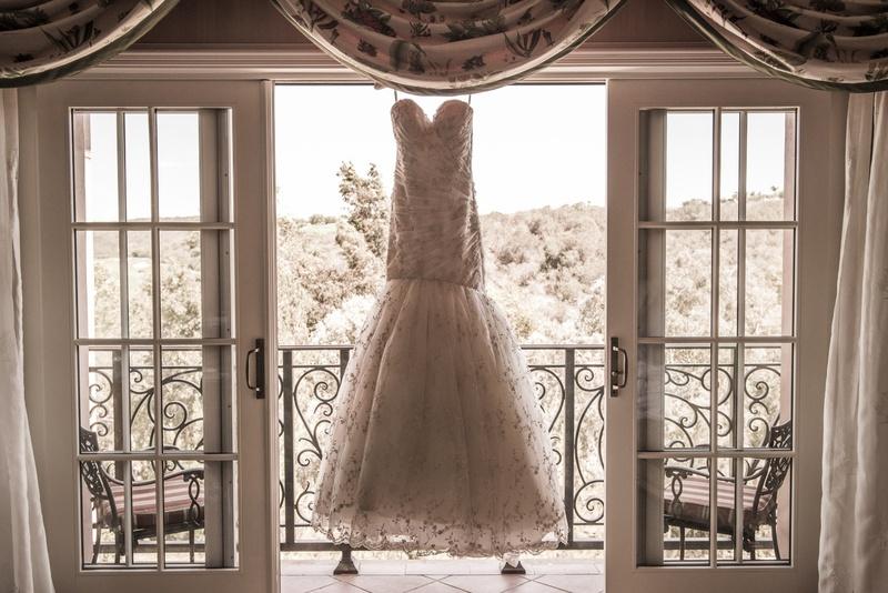 Romona Keveza beaded mermaid wedding dress hangs in window of Grand Del Mar