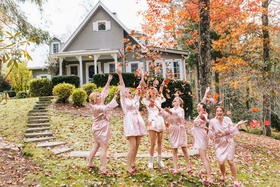 bride and bridesmaids dressed in pink and white robes throw fall leaves into their air outside