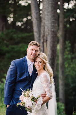 Bride in Oleg Cassini dress with navy blue groom in forest