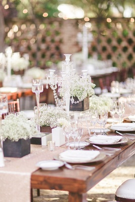 Wood table with sequin runner and cube boxes of white flowers