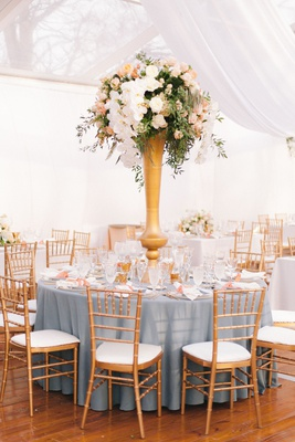 wedding reception blue linen round table gold chairs tall centerpiece white orchid peach flowers