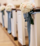 Wedding ceremony church pews decorated with white hydrangeas, pink roses, and blue ribbon