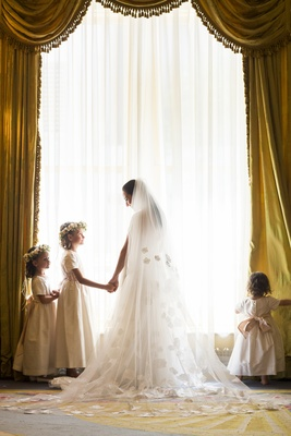 Bride holding flower girl's hand with flower crown