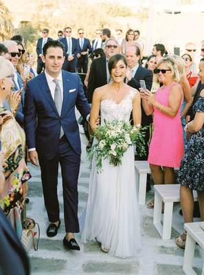 bride in one shoulder mira zwillinger wedding dress carine's bridal atelier with groom in blue suit