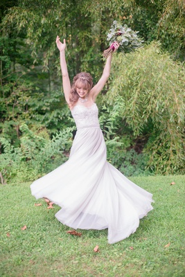 bride twirling in A-line gown beaded bodice sweetheart neckline rustic bouquet