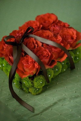 Bright orange and green flowers with brown ribbon