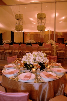 Round table with pink linens, gold glassware, and orchid centerpiece
