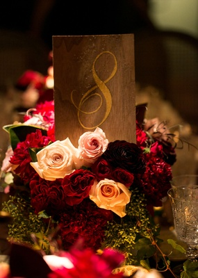 Wood table number on top of roses with gold calligraphy number