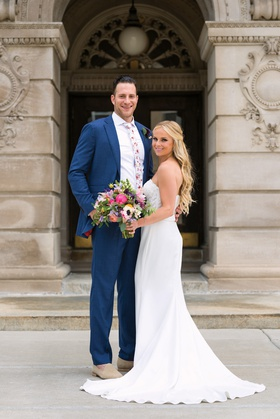 bride in strapless lihi hod bridal gown carrying colorful bouquet, groom in blue suit & floral tie
