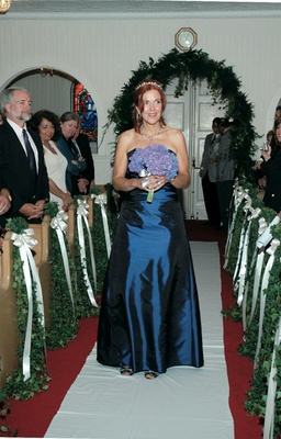 Bridesmaid walks down ceremony aisle in blue dress